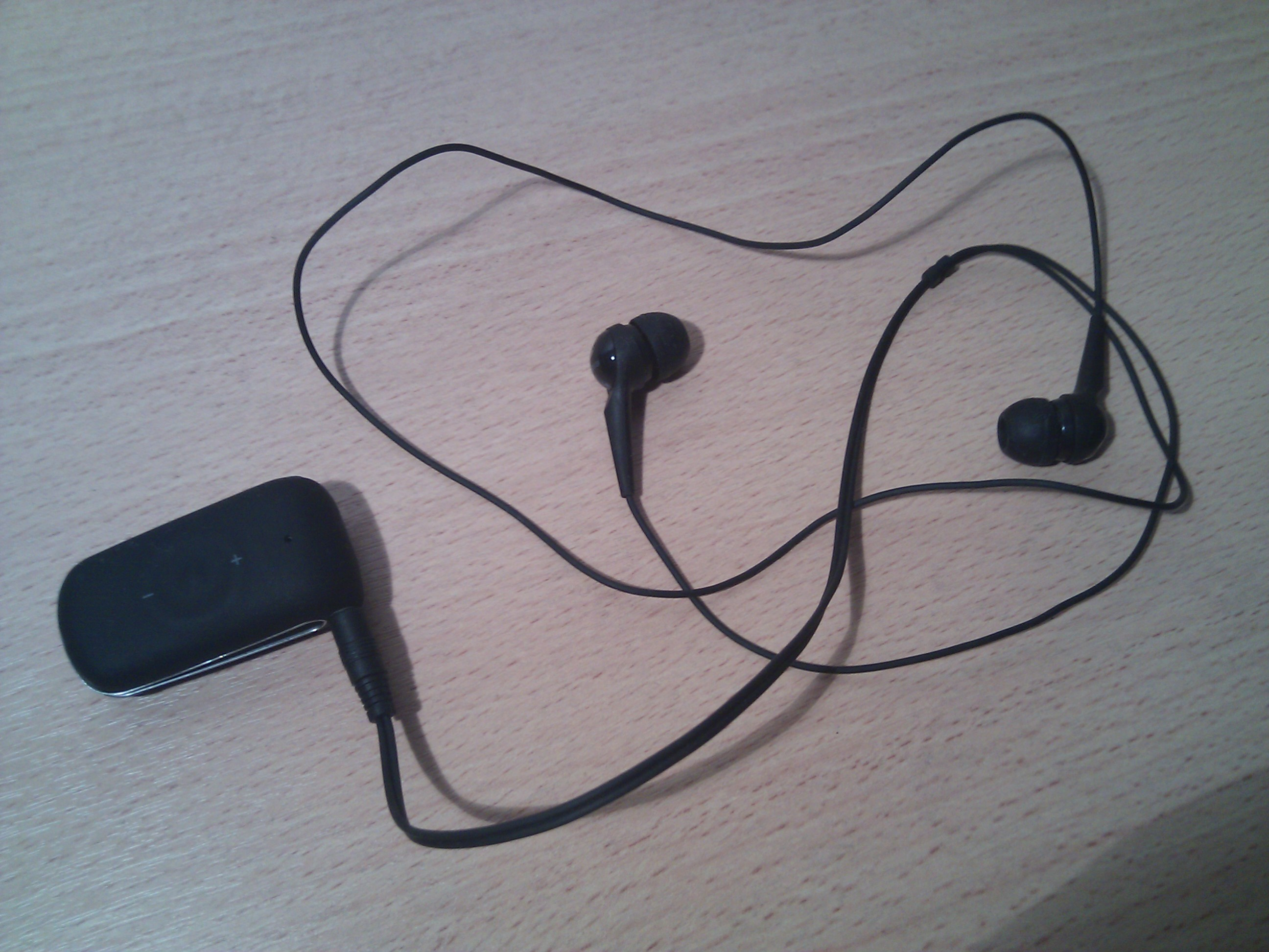 The Jabra Clipper, a Bluetooth headset, with earphones plugged into it.